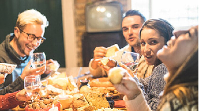 Family eating at dinner table together for holiday family gathering