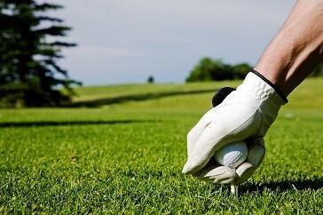 golfer glove putting ball on tee
