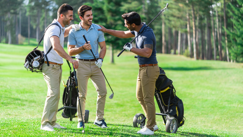 threesome of golfer guys holding clubs