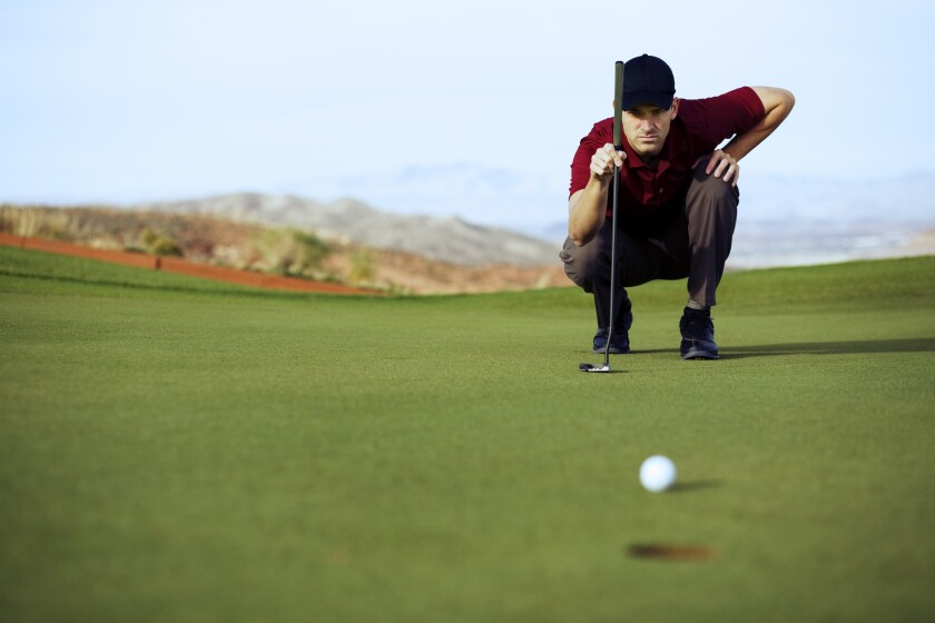 Single Male Golfer lines up his eagle putt.